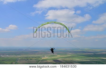 Paraglider sportman flies in the blue summer sky