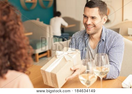 Date in cafe. Lovely couple in cafe with stylish interior. Man and woman having glasses of wine. Man presenting gift to woman and smiling