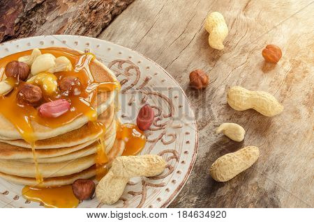 Stack Of Hot Pancakes With Nuts And Caramel Syrup.