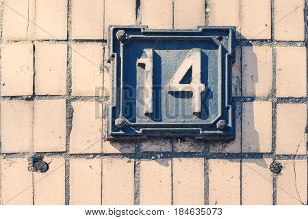 Retro Metal Plate With Drawings 14 On A White Brick Wall, Old House, House Number Index. Suitable As
