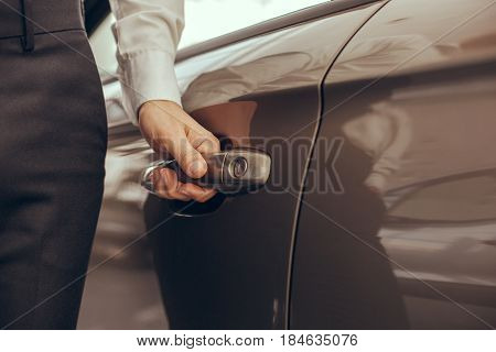 Young man standing near the car holding door rental service