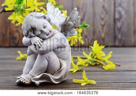 Angel guardian sleeping and yellow spring flowers