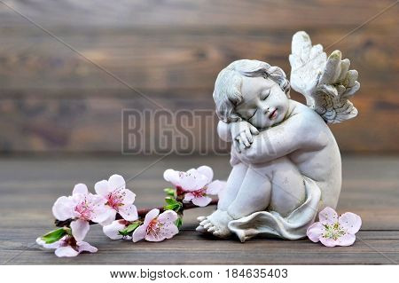 Angel guardian sleeping and spring flowers on wooden background