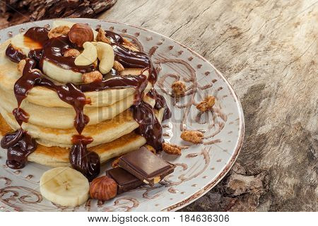 Stack Of Hot Pancakes With Nuts, Bananas And Chocolate Syrup.