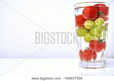 Cherry tomatos and grapes in a glas with water and air bubbles.