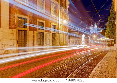 Traditional old street in the night illuminated with tram tracks in Lisbon. Alfama district. Portugal.