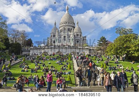 PARIS FRANCE - APRIL 1 2017: Tourists on the hillside of Montmartre on the background of the Sacre-Coeur basilica. The beginning of April. Paris France.
