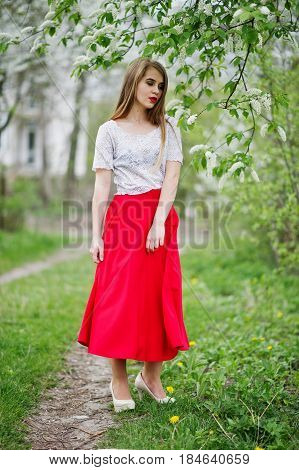 Portrait Of Beautiful Girl With Red Lips At Spring Blossom Garden, Wear On Red Dress And White Blous