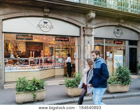 STRASBOURG FRANCE - APR 27 2017: Couple walking in front of Porcus Restaurant on 6 Place du Temple Neuf - specialized restaurant in meat and meat products as sausages steaks etc.