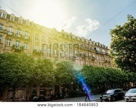 STRASBOURG FRANCE - APR 27 2017: View from below of Avenue de la Marseillaise boulevard with typical French buildings cafe restaurants and pedestrians walking - beautiful sun flare