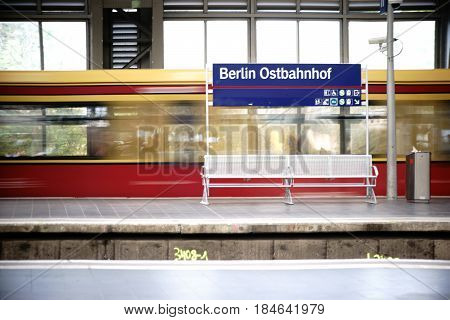 BERLIN, GERMANY - MAY 01: A platform of the Berlin East railway station with a lattice bench as well as a incoming tram on May 01 2017 in Berlin.