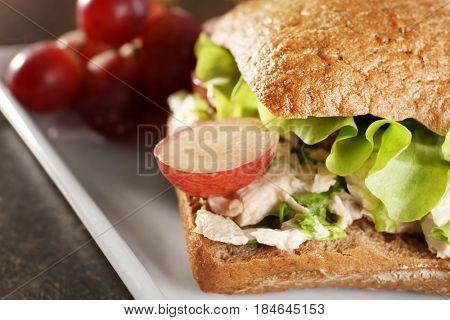 Plate with chicken salad in burger bun, closeup