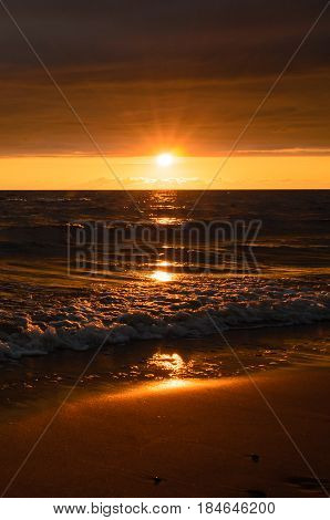 Bright sunset after the storm in the Baltic sea in summer. Sun shines above horizon.