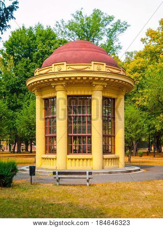 Park gazebo with red roof and yellow facade, Terezin, Czech Republic.