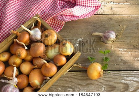 Box with a onions on an old door . Harvest of onion. Agriculture and horticulture. Onion as background texture
