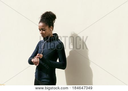 Young woman checking activity tracker on her wrist during outdoor exercise, standing at wall
