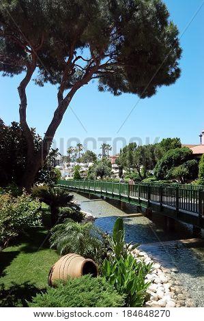 Belek Turkey - June 01 2015: Landscape view of pine bridge cascading watercourse in Bellis Deluxe hotel in Turkey.