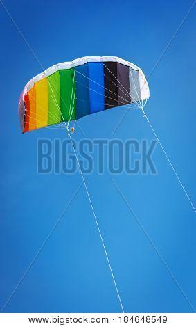 Kite parachute rainbow colors fly high in the sky