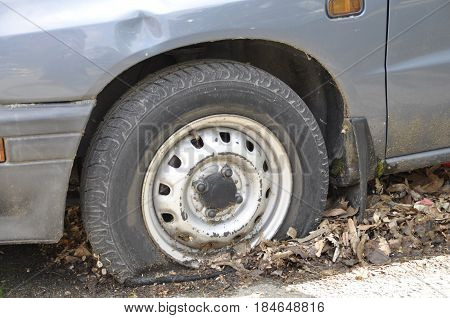 A car with an emergency standing for a long time in the fall unattended with a wheel