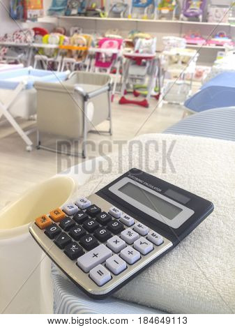 Expenses calculation for new baby coming concept. Electronic calculador at baby furniture shop