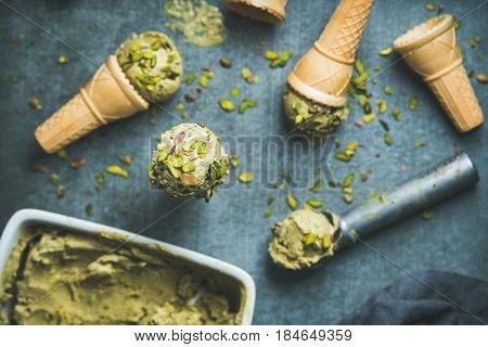 Homemade pistachio ice cream in ceramic mold and metal scooper, with crashed pistachio nuts and waffle cones over dark concrete background, top view, selective focus