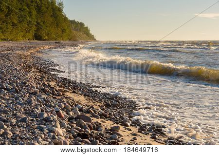 Great summer evening on the stony beach with strong waves.