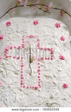 Gluten-free cake with a cross on it in white and pink on Easter Sunday.