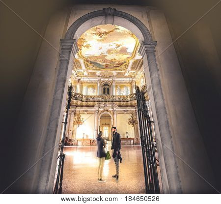 Stra Italy 25 April 2017: a young couple chat inside a large and regal hall of Villa Pisani