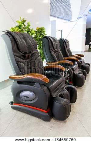 Three black leather comfortable massage chairs in bright light interior. Vertical image