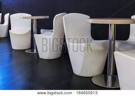 Modern stylish restaurant area with white chairs and tables for lunch or dinner, dark wall and Dark blue tiles