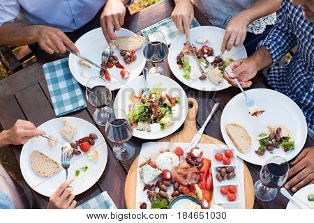 Friends enjoying eating lunch together outdoor. Top view of mature friends hands having lunch with wine and salad. High angle view of dishes with food and people eating salad, food and wine.