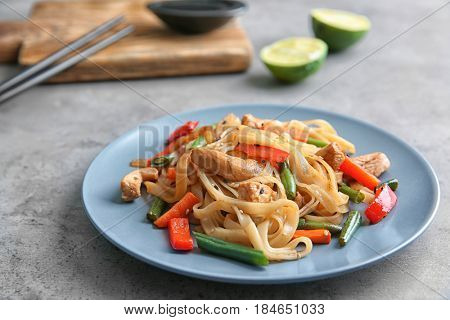 Blue plate with delicious rice noodle on grey table