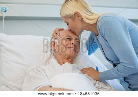 Daughter kissing senior father on forehead in hospital bed. Old dad patient being kissed by daughter while recovering from disease in clinic. Lovely woman visiting old father at medical clinic.