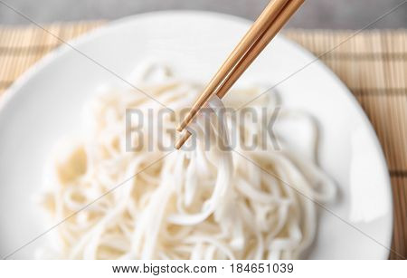 Chopsticks carrying delicious rice noodle on blurred background
