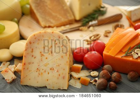 Sliced assorted cheese with nuts on wooden table