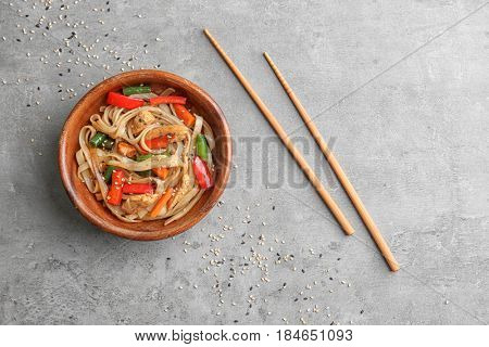 Wooden plate with delicious rice noodle and vegetables on grey background