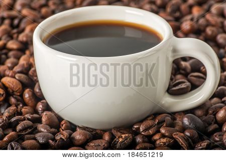 Black Coffee In White Cup, Against A Background Of Brown Coffee Beans, Coffee Background, Aromatic C