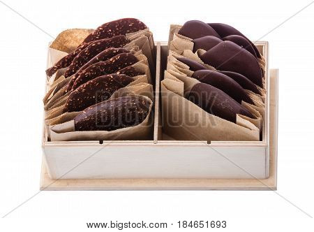 Pieces of dark chocolate in individual paper packaging in wooden box