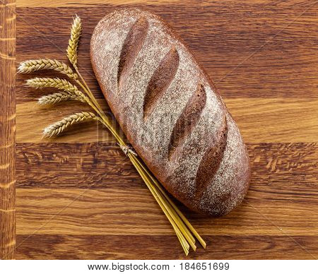 Loaf of bread and rye cones over wooden background