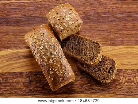 Loaf of homemade bread and slices on wooden background