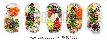 Selection of different kinds of cheese and fish with greens and vegetables. Range of plates over white background.