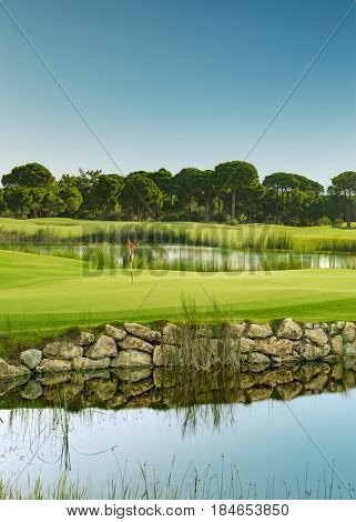 Golf course with lake and trees in the morning