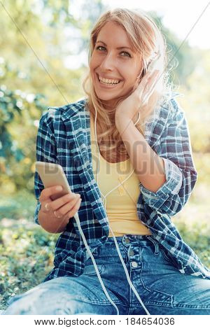 Young woman listening to music on a smart phone outdoors.