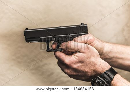 Hands holding and aiming a pistol with finger on trigger.