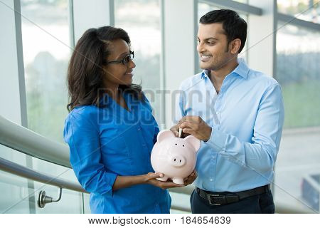 Closeup portrait two smart professionals in blue shirts holding piggy bank isolated office indoors background. Powerful financial and banking business solutions decisions concept