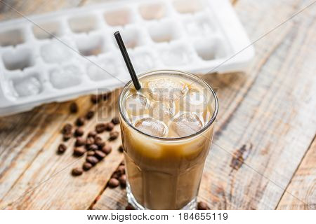 coffee break with cold iced latte and beans in caffee on wooden table background