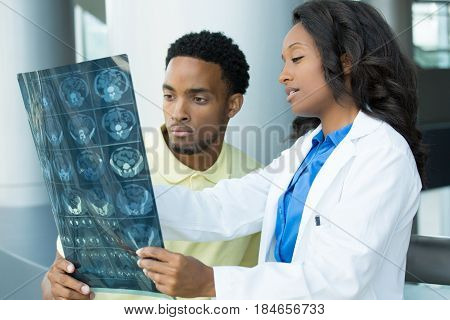 Closeup portrait of intellectual healthcare professionals with white labcoat looking at full body x-ray radiographic image ct scan mri isolated hospital clinic background. Radiology department