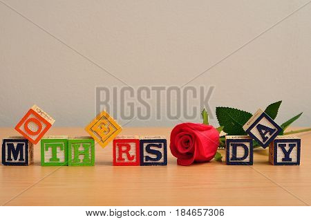 Mothers day spelled with colorful alphabet blocks and a red rose