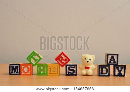 Mothers day spelled with colorful alphabet blocks and a white teddy bear
