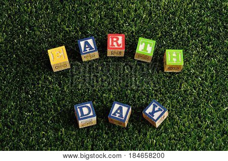 Earth day spelled with colorful alphabet blocks isolated on artificial grass